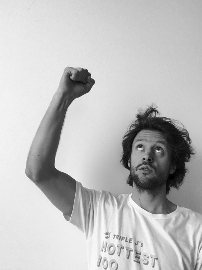 Brent raising his right fist in the air while looking up. Black and white image.